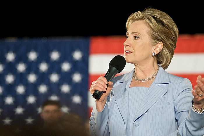 Hilary Clinton giving a speech in front of the Amerian flag.