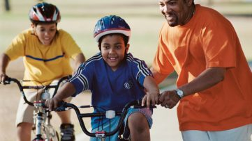 A father and his child cycling.