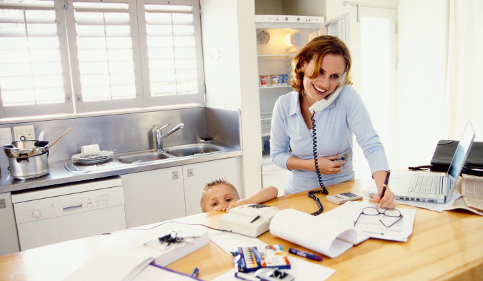 Woman on phone in kitchen with kid.