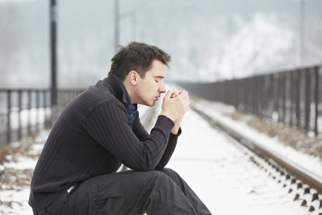 A sad man sitting on train tracks