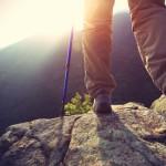 Woman hiker legs stand on mountain peak rock