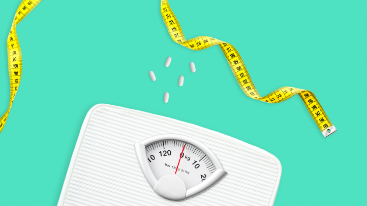 A scale with pills represents phentermine for weight loss